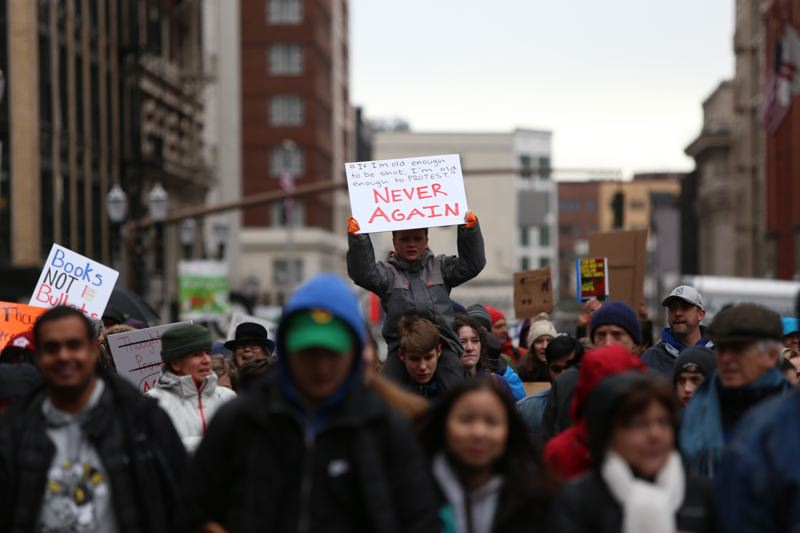 TRIBUNE PHOTO: JESSIE DARLAND - A young boy carries a sign reading 'Never Again' during the March for Our Lives on Saturday, March 24 in downtown Portland.