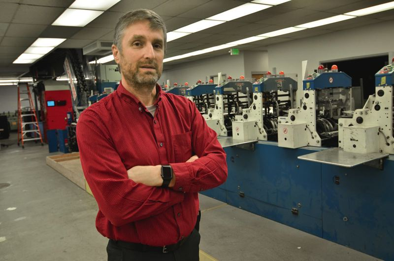 PAMPLIN MEDIA GROUP: VERN UYETAKE - Don Atwell, general manager of printing operations for Pamplin Media Group, shows off new equipment that signficantly increases efficiency and the capacity to insert advertising supplements and coupons.