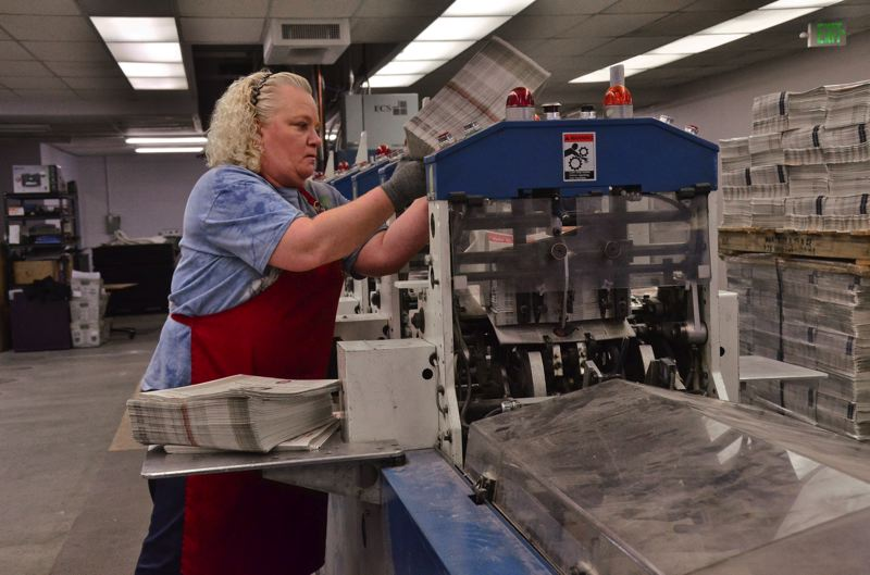 PORTLAND MEDIA GROUP: VERN UTETAKE - Pamplin Media Group employee Leah Robinson feeds a bundle of newspapers into the GMA SLS 1000 inserter at the Division Street press operations. The machine is part of a major remodel and expansion of the facility to accommodate printing 23 PMG newspapers while adding capacity for commercial printing work.