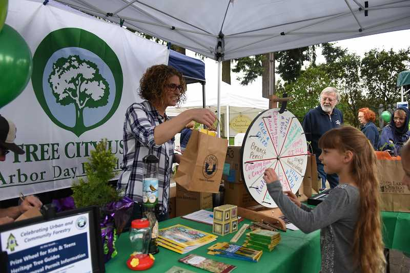 PHOTO COURTESY OF OREGON COMMUNITY TREES - Contract arborist Morgan Holen hands a prize to a young visitor during Lake Oswego's Arbor Week celebration in 2017. This year's festivities kick off April 2 with a tree planting at Stafford Grove Park.