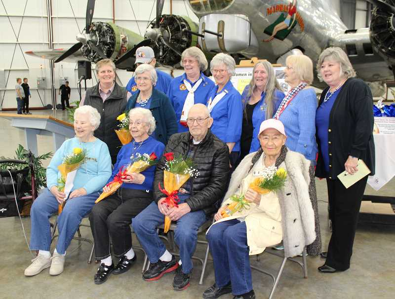 HOLLY M. GILL - Participating in the Rosie the Riveter ceremony at Erickson Aircraft Collection were honorees, front left to right, Irene Prince, June and Loyal Miller, and Catherine Shaw, and back left to right, Michelle Forster, Dennis Hanson, Dorothy Burgess (honoree), Judith Bowden, Judy Hellwig, Denise Keegan, Louise Muir and Judy Berg.