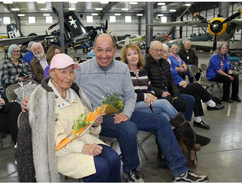 HOLLY M. GILL - Catherine Shaw, 94, with her son, Dennis, is honored with a bouquet of roses during 'Rosie the Riveter Day' on March 21, at Erickson Aircraft Collection.