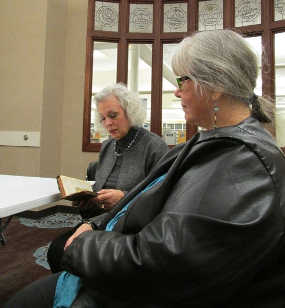 OUTLOOK PHOTO: TERESA CARSON - Sarah Eckstein reads the 23d Psalm from her mothers Bible at the monthly peace vigil held at the Gresham Library, as Jan Hall listens.