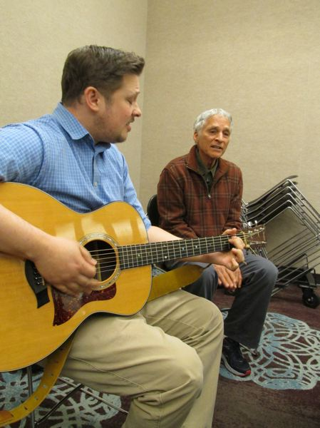 OUTLOOK PHOTO: TERESA CARSON - Brendon Bassett and his father Robert sing a song of Roberts composition based on Bahai teachings.
