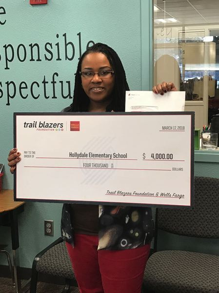 CONTRIBUTED PHOTO: GRESHAM-BARLOW SCHOOL DISTRICT - Hollydalle Elementary fourth grade teacher Chastity Clegg picks up the big check for $4,000 from the Portland Trail Blazers Foundation and Wells Fargo at the Blazer game on Saturday, March 17.