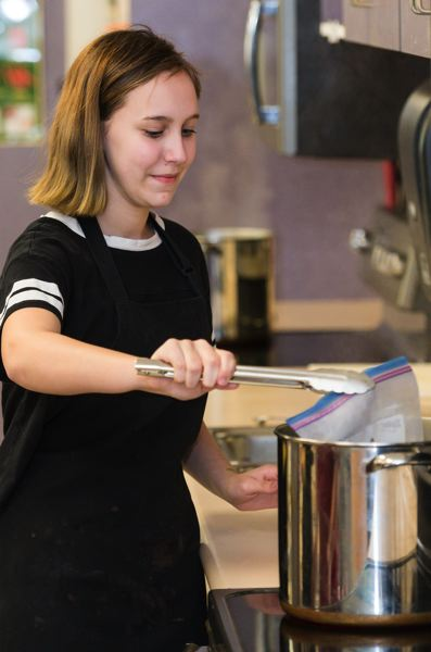 STAFF PHOTO: CHRISTOPHER OERTELL - Kylee DuBois, 14, places a bag filled with eggs for an omelette into boiling water during the culinary arts class at Century.
