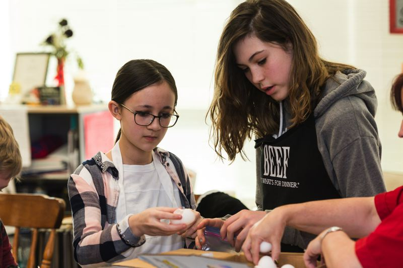 STAFF PHOTO: CHRISTOPHER OERTELL - Kristin Sine, 12, and Logan Kerner, 12, crack eggs into a bag during the class, where they learned how to make omlettes in a bag.