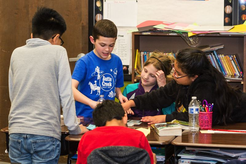 STAFF PHOTO: CHRIS OERTELL - Fourth grade students at McKinney work together in table groups playing a card game about what it takes to maintain apple trees.