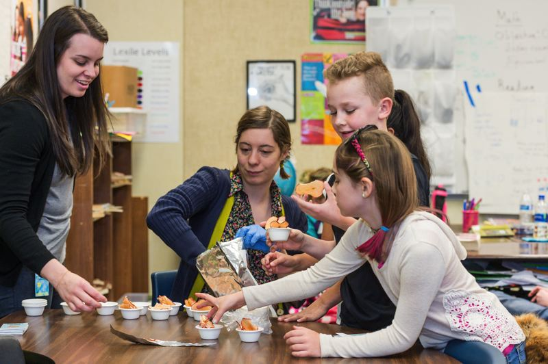 STAFF PHOTO: CHRIS OERTELL - Jessica Jansen and Kassia Rudd from the Oregon Agriculture in the Classroom Foundation hand out dried apple slices to fourth grade students during the event.