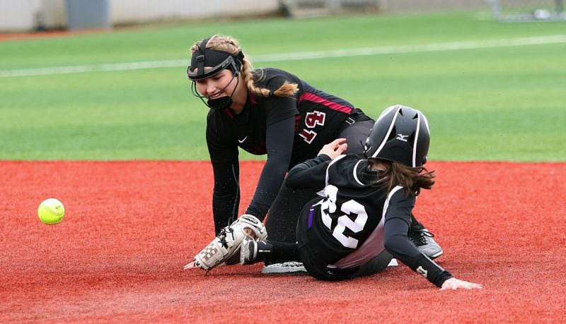 DAN BROOD - Tualatin freshman Taylor Corcoran (14) reaches for the ball as South Eugene's Sydney Crabbe slides to second base during Tuesday's game.