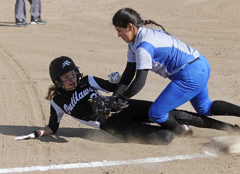 WILL DENNER/MADRAS PIONEER - Madras third baseman Genesis Wuiroz, right, tags a Sisters baseerunner during the March 20 game in madras.