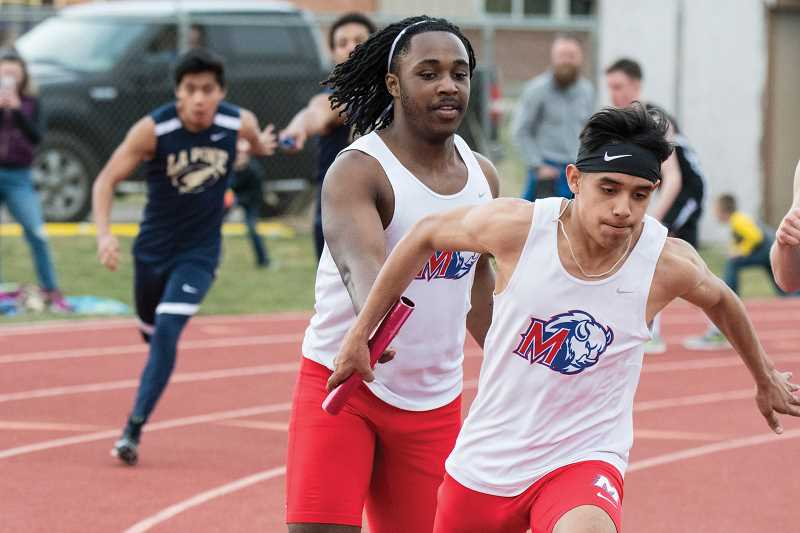 LON AUSTIN/FOR THE PIONEER - Madras sophomore Treyvon Easterling (back) passes the baton to freshman Leo Gutierrez (front) in a relay event during the Crook County Relays on March 21, in Prineville.