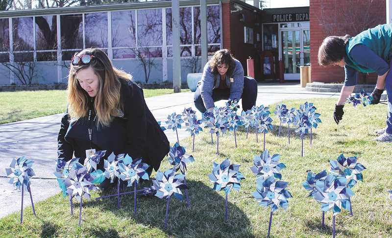 JASON CHANEY - Volunteers kicked off Child Abuse Prevention Month in Prineville by planting pinwheel gardens at the Prineville Police Department and other community locations. Pictured left to right are Heather Stuart, Debbie Seiffert and Nancy Eck.