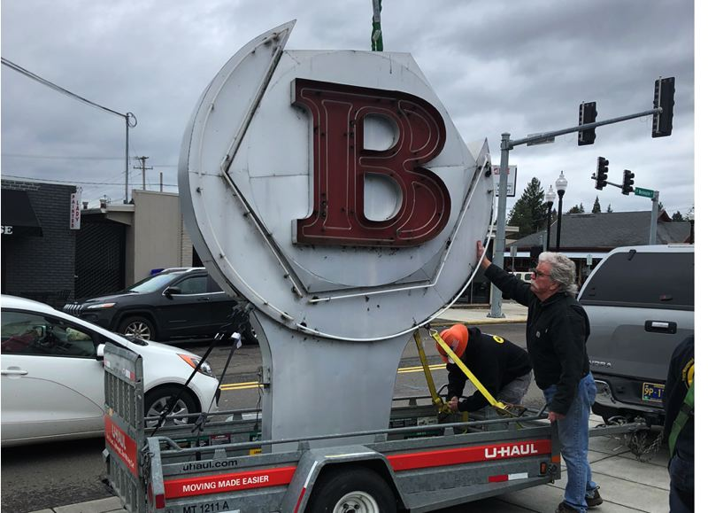 SUBMITTED PHOTO - Michael DeWitz accepts the old Bernard's Garage sign on behalf of the Milwaukie Museum. He and other citizens have long admired how the automotive shop's sign is shaped like a wrench moving a bolt.