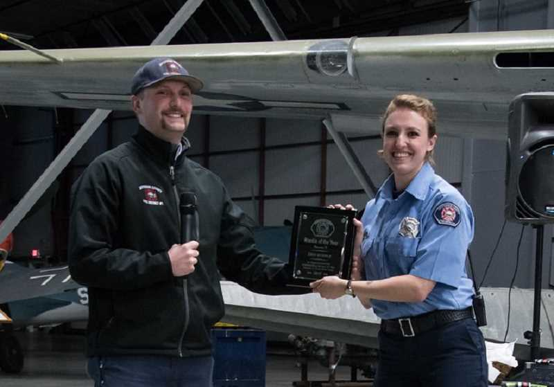 SUBMITTED PHOTO - Zack Leeper, the Firefighter of the Year, hands out the Rookie of the Year award to Erin Hurdle.