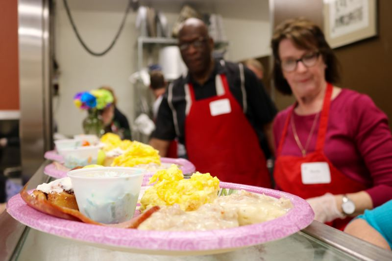TRIBUNE PHOTO: ZANE SPARLING - Volunteer prepare a hot meal of scrambled eggs, biscuits and gravy and salad at the Union Gospel Mission in downtown Portland on Easter Sunday, April 1.