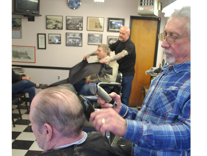 PHOTO BY RAYMOND RENDLEMAN - Barbershop owner Al Kelley trims a customer's hair while Dean Bollinger gets another customer ready for a haircut.