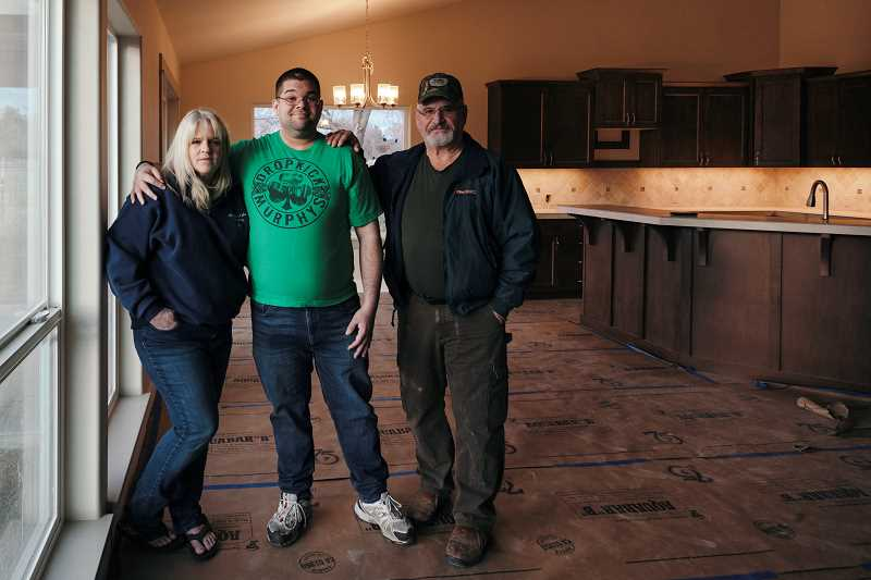 PHOTO BY CHERYL MCINTOSH - Vetarn Ryan Craig and his parents, Jennifer and Ron Miller, stand in the home that are having built.