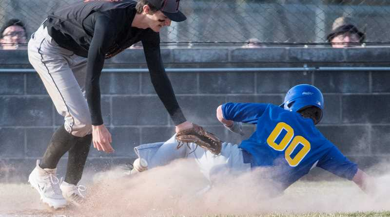 LON AUSTIN/CENTRAL OREGONIAN - Diego Smith slides safely into home during the Cowboys' 18-9 victory over Taft Thursday afternoon. The Cowboys went 3-0 at the Madras Spring Break Tournament, winning the event.