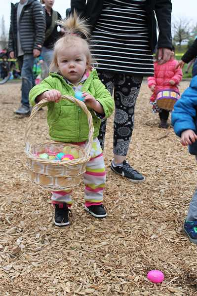 OUTLOOK PHOTO: ANNE ENDICOTT - Eighteen-month-old Lucy Hendrickson gathers quite a basket of candy-filled eggs at City Park Churchs 16th annual Easter Egg Hunt Sunday, April 1, at Main City Park in Gresham.