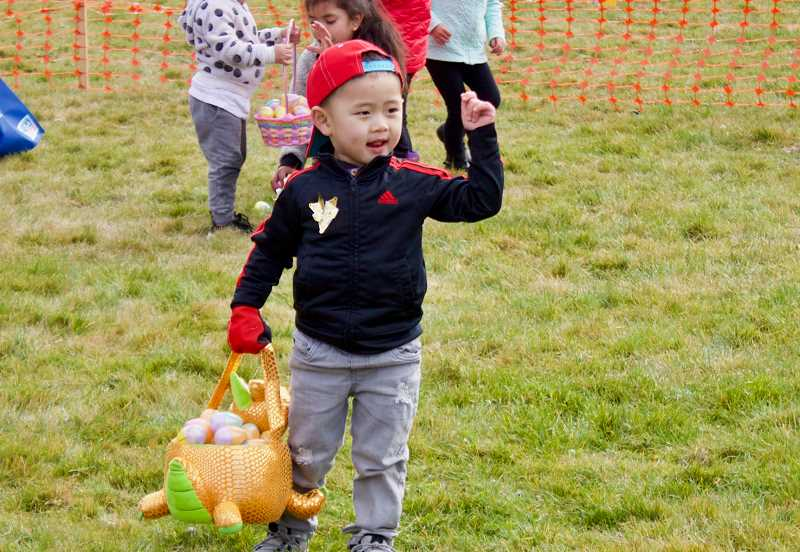 OUTLOOK PHOTO: CHRISTOPHER KEIZUR - Three-year-old Philemon celebrates a successful Easter Egg Hunt Saturday morning, March 31, in Wood Village.