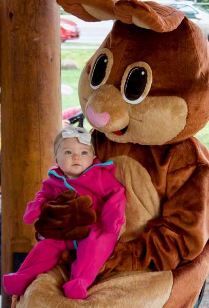 OUTLOOK PHOTO: CHRISTOPHER KEIZUR - Nine-month-old Karsyn Berg meets the Easter Bunny for the first time during the Wood Village Easter Egg Hunt.