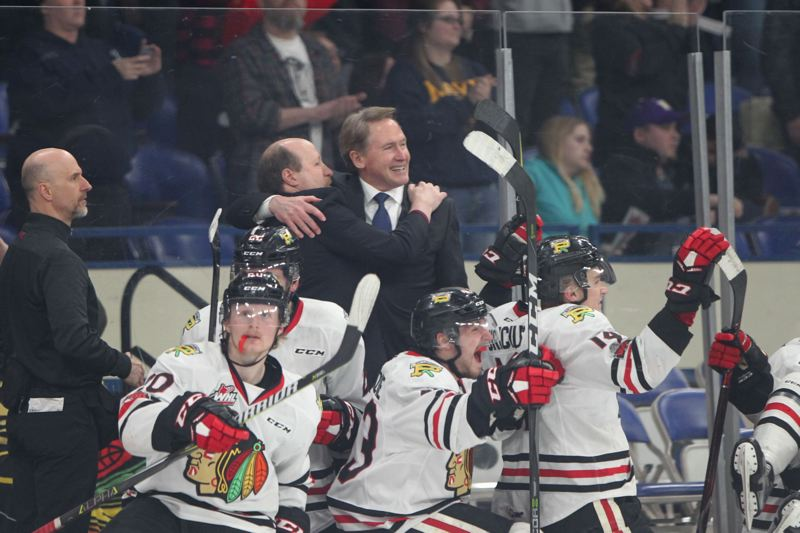 TRIBUNE PHOTO: JAIME VALDEZ - Portland Winterhawks head coach Mike Johnston (right) gets a hug from assistant coach Danny Flynn behind the bench at the end of Tuesday's Game 7 against the Spokane Chiefs. Portland won the deciding game of the WHL first-round series, 3-1, at Memorial Coliseum.
