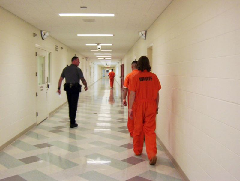 FILE PHOTO - A Washington County sheriff's deputy escorts inmates through a passageway in the county jail.