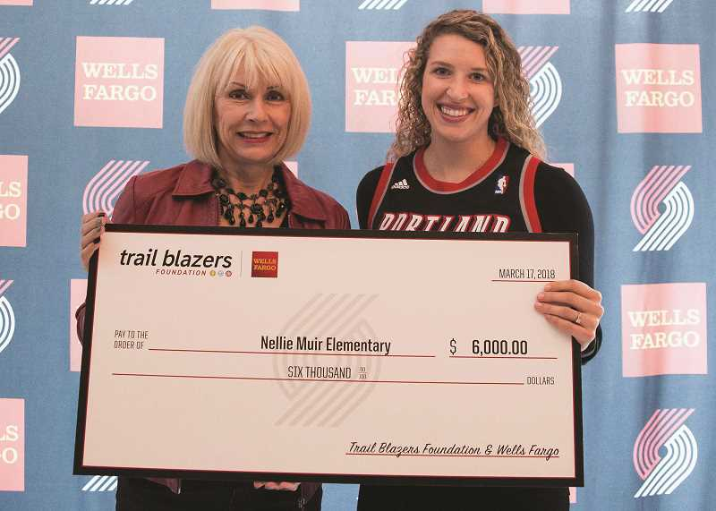 COURTESY PHOTO: WELLS FARGO - Meghan Day (right), a teacher from Nellie Muir Elementary School, receives a check for $6,000 from Wells Fargo Region Bank President Tracy Curtis on March 17 at the Moda Center arena in Portland.