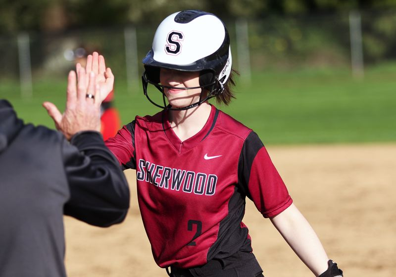 TIMES PHOTO: DAN BROOD - Sherwood junior Sarah Lesch gives a high five to first base coach Mike Brice after singling in a run during the game with David Douglas on Monday.