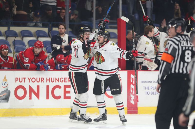 TRIBUNE PHOTO: JAIME VALDEZ - Kieffer Bellows (right) of the Portland Winterhawks receives congratulations from teammate Brendan De Jong after Bellows scored what would be the game-winning goal Tuesday night in Game 7 against the Spokane Chiefs. The Hawks won, 3-1, at Memorial Coliseum to take the Western Hockey League first-round series, 4 games to 3.