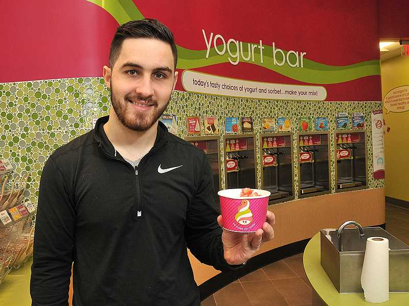 STAFF PHOTOS: VERN UYETAKE  - Menchie's Frozen Yogurt franchise owner Igor Mytryk poses before the shops wall of frozen yogurts, toppings and sauces. The frozen yogurt store focuses on making smiles happen.