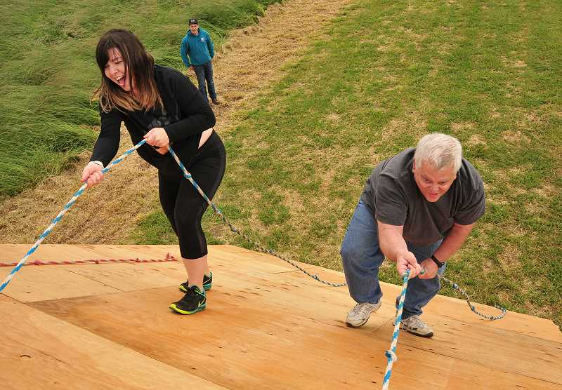 REVIEW PHOTO: VERN UYETAKE - Jamie Inglis and Lake Oswego Review Editor Gary Stein scale an obstacle at Luscher Farm, site of the Howl at the Moon 5K course.