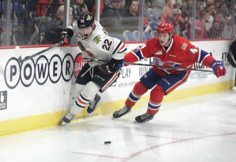 TRIBUNE PHOTO: JAIME VALDEZ - Kieffer Bellows (left) of the Portland Winterhawks tries to get around Jeff Faith of the Spokane Chiefs during Game 7 of their series Tuesday night at Memorial Coliseum.