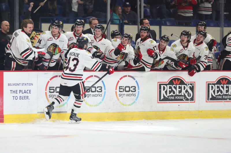 TRIBUNE PHOTO: JAMIE VALDEZ - Skyler McKenzie high-fives teammates on the Portland Winterhawks bench after scoring late in Tuesday's Game 7 against Spokane and giving the home team a 3-1 lead at Memorial Coliseum.
