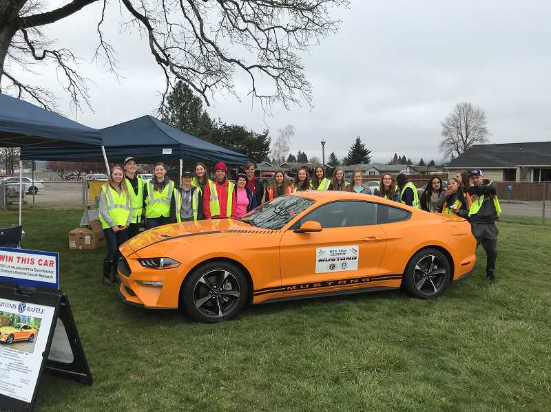 SUBMITTED PHOTO: CHARLIE WILLIAMS - The key club and Kiwanis members gather for a photo with the raffle car, a custom Mustang.