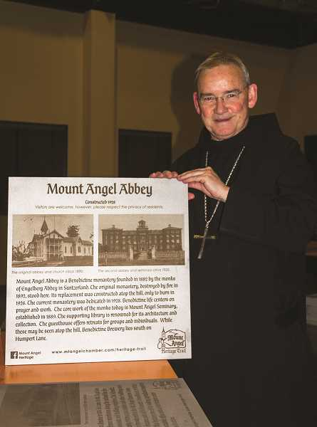 WOODBURN INDEPENDENT - The Abbot of Mount Angel Abbey and Seminary the Rt. Rev. Jeremy Driscoll holds one of the new signs for Mount Angel's Heritage Trail.