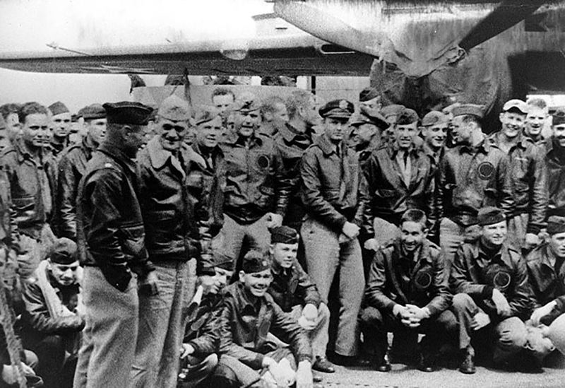 CONTRIBUTED PHOTO - U.S. Navy Capt. Marc A. Mitscher, skipper of the USS Hornet aircraft carrier (standing in the left foreground with the paper in his left hand) chats with Lt. Col. James Jimmy Doolittle. They are surrounded by the airmen who will soon fly their bombers off this aircraft carrier knowing that this perilous secret attack bombing run will be a one-way only mission. They are well aware that none of their 16 bombers will have enough fuel to return to the ship. These brave men will become known as the legendary Doolittles Raiders.