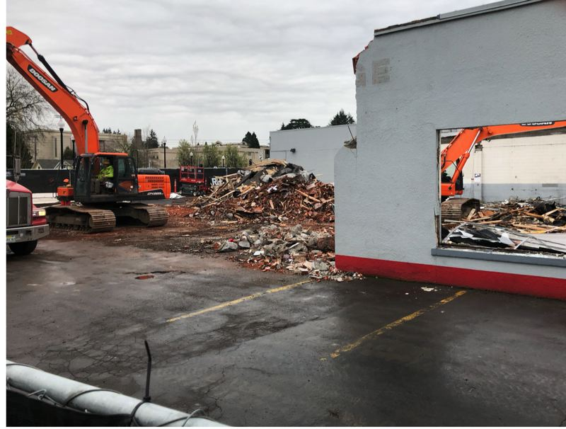 SUBMITTED PHOTO - Bernard's Garage is only left as 'GE' as demolition is almost completed on its facade. The iconic auto-repair shop is at the corner of 21st Avenue and Washington Street, the same intersection where the historic Milwaukie High School building (in background) will also soon be demolished.