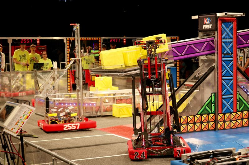 TRIBUNE PHOTO: ZANE SPARLING - Student-controlled robots lift 'power cubes' made of milk crates onto a scale during the FIRST Robotics regional championship on Saturday, April 7 in Portland.