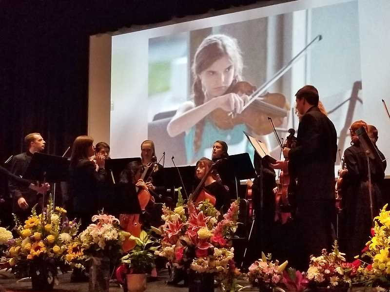 REVIEW PHOTO: GARY M. STEIN - With an image of a young Nina Heidgerken behind them, members of the Lakeridge High School orchestra prepare to play the somber yet uplifting song 'Rise' at her Celebration of Life on Sunday.