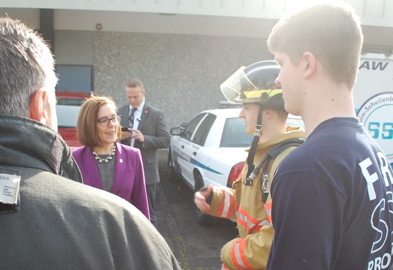 PHOTO BY: RAYMOND RENDLEMAN - Sabin firefighting teacher Neal Dietz, along with students Noah Stevens and Benjamin White, meet with the governor.
