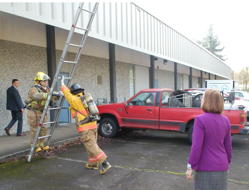 PHOTO BY: RAYMOND RENDLEMAN - Gov. Kate Brown watches firefighting students demonstrate ladder use.
