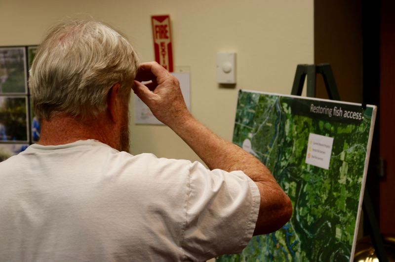 OUTLOOK PHOTO: ZANE SPARLING - Sweetbriar Lane resident Steve Smith examines a poster describing the Cochran Road bridge during a meeting at Mt. Hood Community College on Tuesday, March 13.