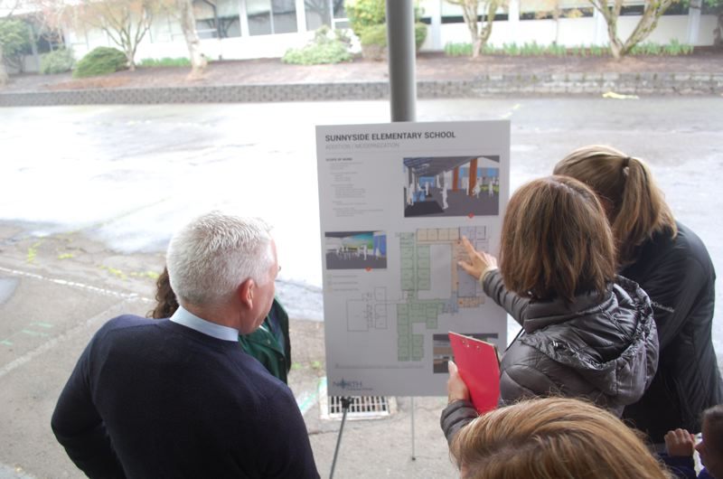PHOTO BY: RAYMOND RENDLEMAN - Attendees of the April 5 groundbreaking event for renovation and expansion at Sunnyside Elementary School point to diagrams as they ask Superintendent Matt Utterback questions.