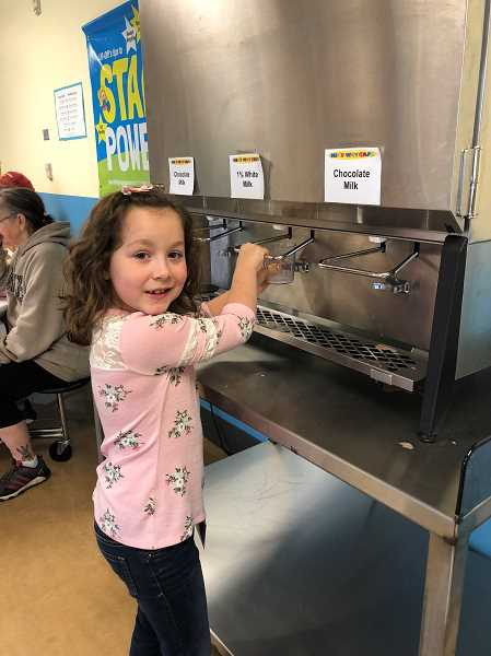 HERALD PHOTO: KRISTEN WOHLERS - Delilah Woodruff mixes chocolate milk with 1 percent milk from the milk machine at Knight Elementary.