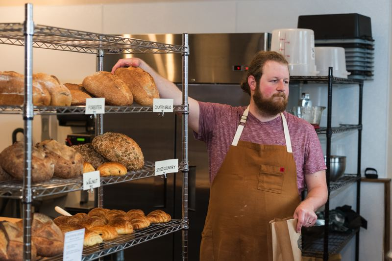 STAFF PHOTO: CHRISTOPHER OERTELL - Slow Rise Bakehouse owner Dave Ferrier selects a loaf of bread for a customer.