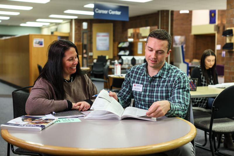 PHOTO COURTESY: CCC - Clackamas Community College Advising and Career Coach Kyle Thomas (right) works with students (including April Allen, left) to get them on a path and stay on track.