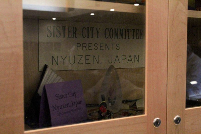 STAFF PHOTO: MARK MILLER - Artifacts and artwork from Nyuzen are displayed in the Forest Grove Community Auditorium behind glass.
