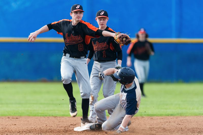 PAMPLIN MEDIA GROUP: CHRISTOPHER OERTELL - Scappoose shortstop J.C. Gross steps on second to get Banks base runner Dakota Bunn in the third inning, but Trask Applegate scores from third on the play in the third inning Monday, giving the Braves a 2-0 lead in their 2-1 victory.